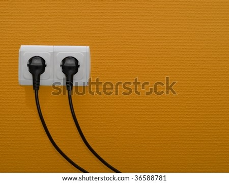 Two electric outlets on orange wall - stock photo