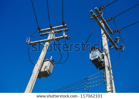 two electric poles with a transformer on a background of blue sky - stock photo