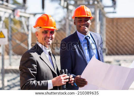 two electrical managers in power plant - stock photo