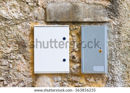 Two electrical plastic junction box against a stone and brick wall - stock photo