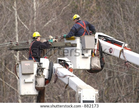 Two Electrical workers in Cherry Picker fixing cables - stock photo
