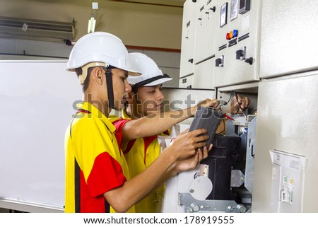 two electrician at work on distribution board - stock photo