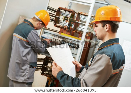two electrician builder engineer works with electric cable wiring of fuse switch box - stock photo