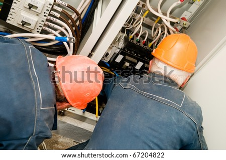 Two electrician man operating personnel installing and mounting new industrial wiring at voltage panel - stock photo