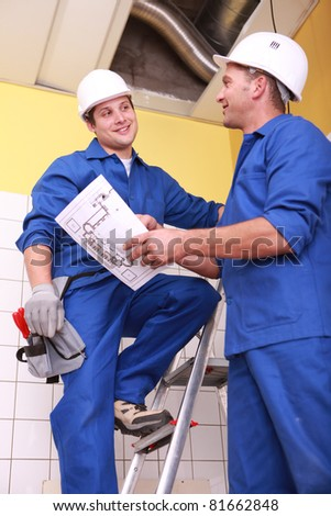 Two electrician repairing ceiling - stock photo