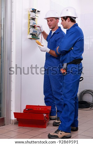Two electricians checking power supply - stock photo
