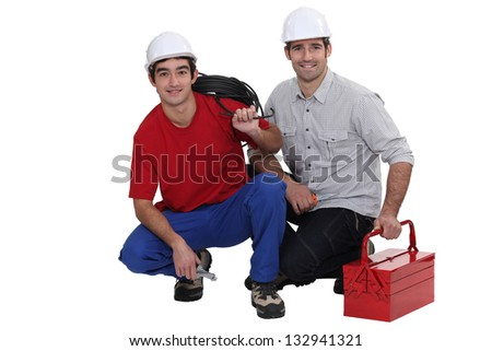 Two electricians crouching down - stock photo