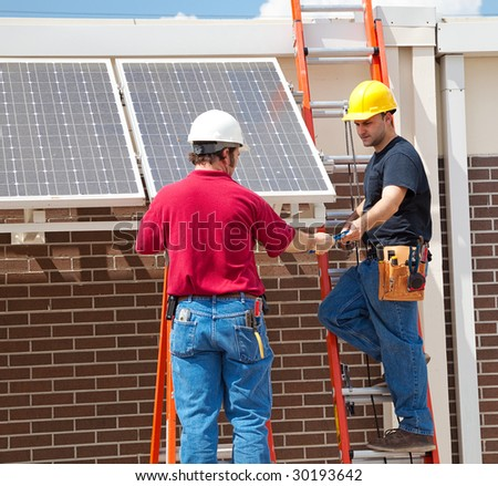 Two electricians installing solar panels on the side of a building. - stock photo