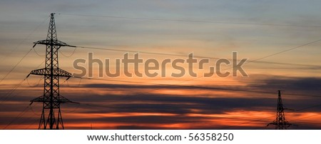 Two electricity pylons. Sunset. - stock photo
