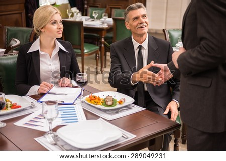 Two elegant business partners shaking hands while having business lunch. Great deal agreement. - stock photo