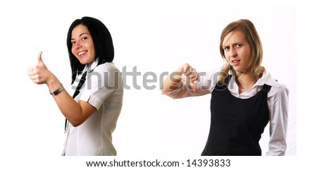 Two elegant businesswomen colleagues are giving the thumbs down and thumbs up. The black-haired lady is smiling but the blond girl is sad. They are wearing stylish shirts. - stock photo