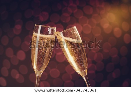 Two elegant champagne glasses making toast on holiday bokeh background