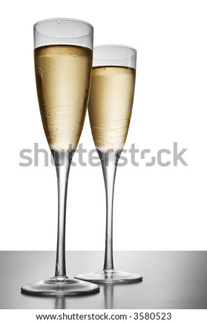 Two elegant champagne glasses on a dark surface - stock photo