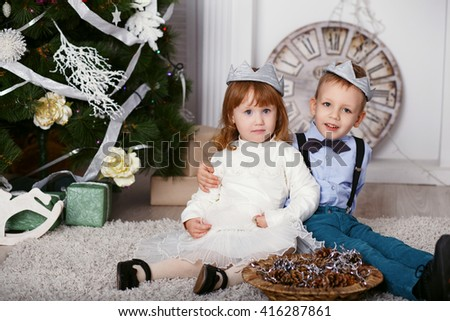 Two elegant little kids in crown. Two elegant little kids decorating Christmas tree with fir-cone. New year preparation. Happy children and family. - stock photo