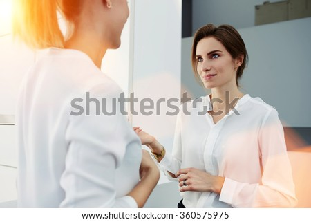Two elegant women entrepreneurs talking about something while standing in modern office interior, intelligent female leaders planning the work schedule for next week while they resting after meeting
