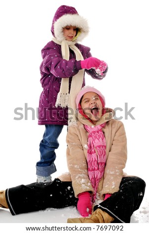Two elementary girls bundled in winterwear playing in snow.  Isolated on white. - stock photo