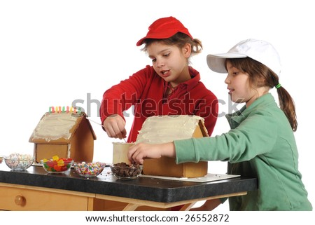 Two elementary girls decorating gingerbread houses together.  Isolated on white. - stock photo