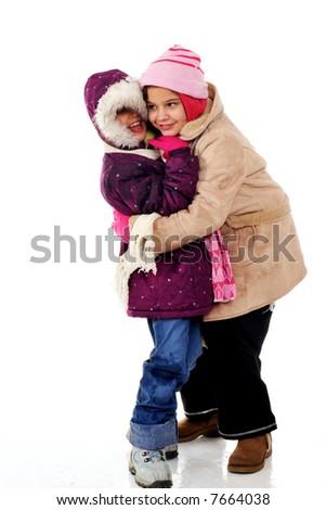 Two elementary girls hugging while bundled in winterwear. - stock photo