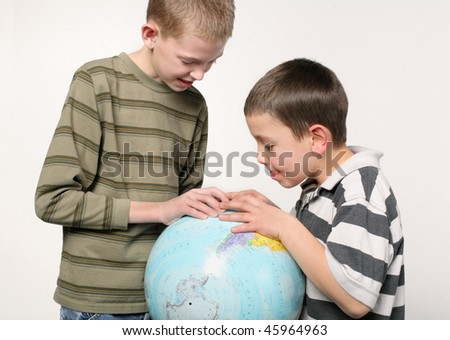 two elementary school age boys looking closely at a world globe - stock photo