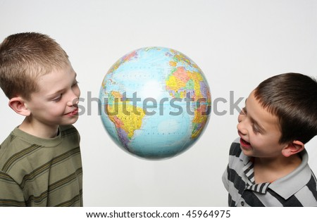 two elementary school age children looking at a world globe suspended in the air - stock photo