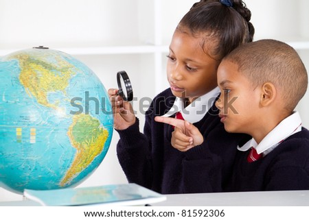 two elementary school students looking at globe - stock photo