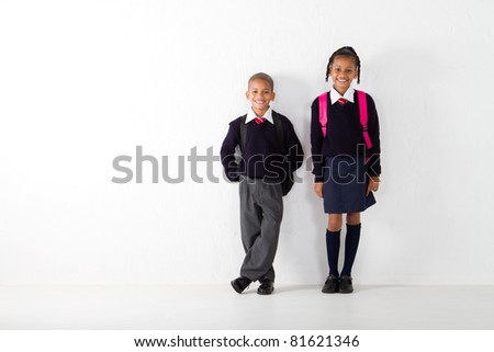 two elementary students standing against wall - stock photo