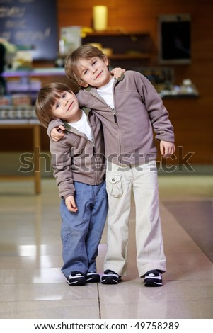 Two embracing little boys in grocery shop - stock photo