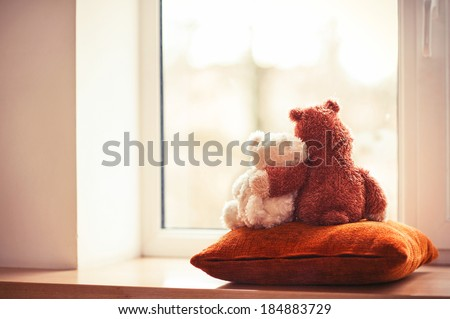 Two embracing loving teddy bear toys sitting on window-sill - stock photo