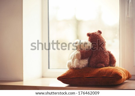 Two embracing teddy bears looking through the window sitting on window-sill. - stock photo