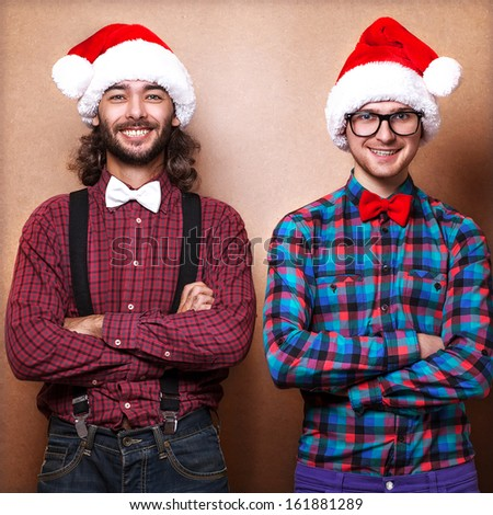 Two emotional Santa Claus dressed in clothes hipster standing near a wall