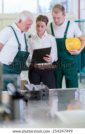Two employees and the boss checking the plan - stock photo