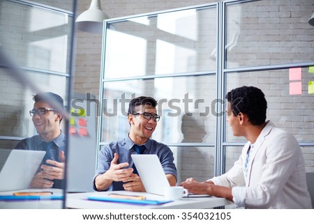 Two employees discussing data at workplace in office - stock photo