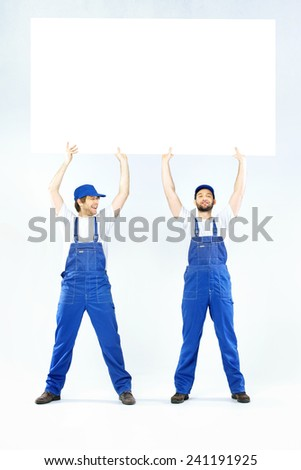 Two employees holding a blank banner - stock photo