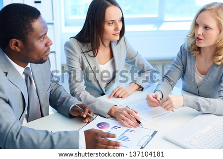 Two employees listening to the business partner while working with papers at meeting - stock photo