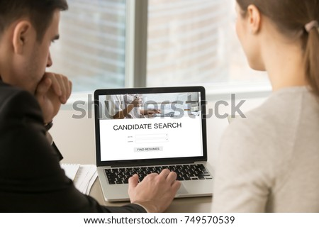 Two employers searching for new job candidates using search engine on laptop. Employers search for new professional staff. Headhunters browsing resumes. Close up view over shoulder, focus on screen.