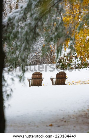 Two empty adirondack chairs on an early snowfall in the autumn, Stowe, Vermont, USA - stock photo
