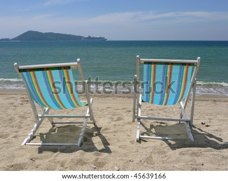 Two empty beach chairs at a tropical beach