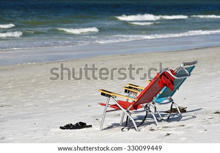 Two Empty Beach Chairs on the Beach facing the Ocean - stock photo