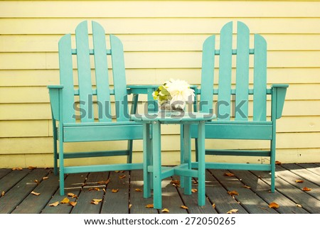 Two empty blue wood adirondack chairs and table with bouquet of flowers in vase on a patio - stock photo