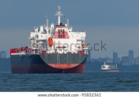 Two empty cargo ships anchored just outside a port. - stock photo