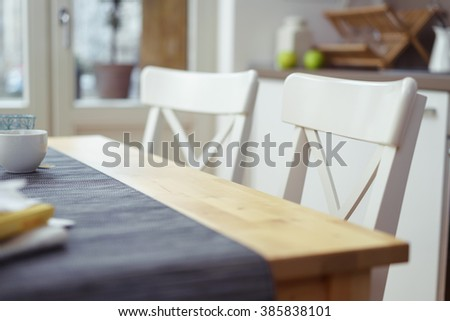 Two empty chairs at a dining table in a house or apartment, selective focus to the one in the foreground - stock photo