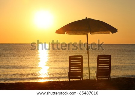 Two empty chairs stand on  beach under  opened umbrella with  view on marine sunset - stock photo