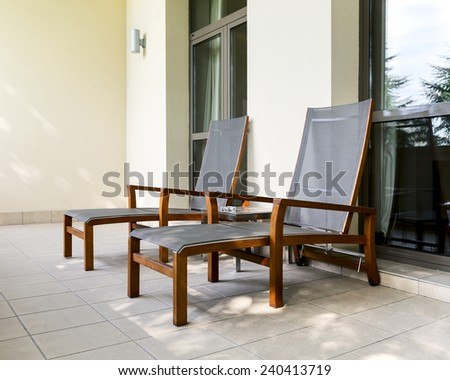 Two empty chaise longue and table on balcony of the hotel - stock photo