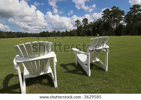 two empty lawn chairs at the edge of the driving range