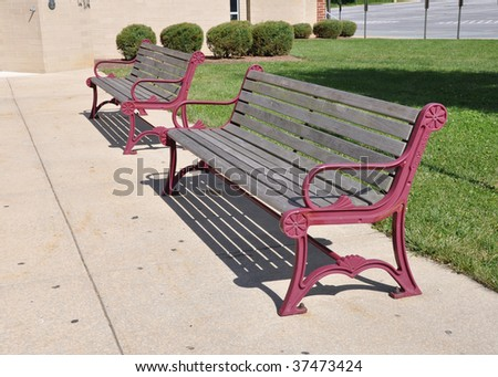 two empty outdoor benches by a concrete walkway