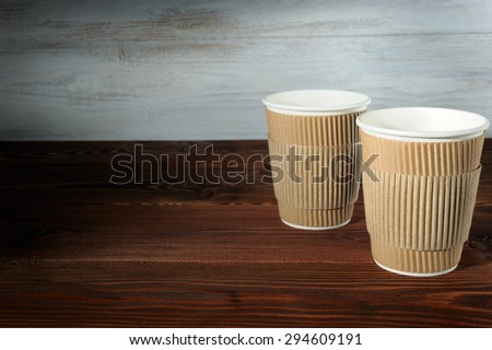 Two empty paper cups on wooden background - stock photo