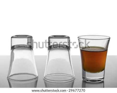 Two empty shots upside down and a third one full of liquor.