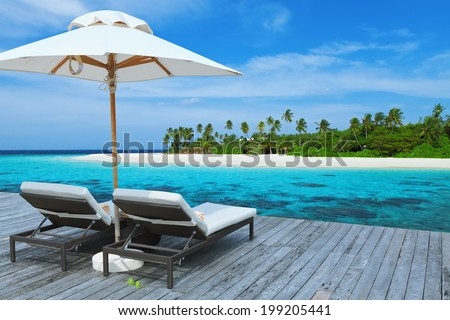 Two empty sunbed on the water villa, beautiful seascape,  relaxation on Maldives Island, luxury summer vacation concept  - stock photo