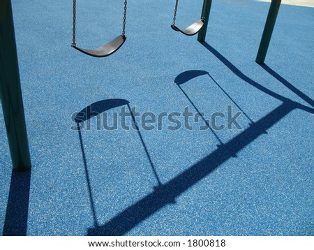 Two empty swing at the playground with a blue background - stock photo