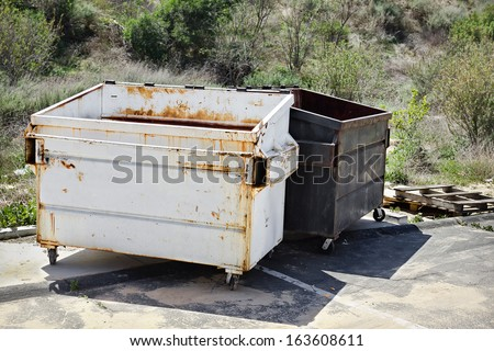 Two empty trash dumpsters sit in a parking lot. - stock photo